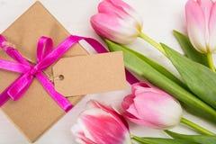dagblomman ger mödrar mumsonen till Rosa tulpan och en gåva för tomt kort på vit bakgrund, bästa sikt, kopieringsutrymme Royaltyfri Fotografi