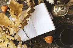 Dagbok kopp av varmt kaffe, hösteksidor, kruka för turkiskt kaffe på en träbakgrund kopiera avstånd cozy isolerad white för höst  fotografering för bildbyråer