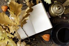 Dagbok kopp av varmt kaffe, hösteksidor, kruka för turkiskt kaffe på en träbakgrund kopiera avstånd cozy isolerad white för höst  royaltyfri fotografi