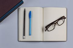 Dagbok med en penna och en blyertspenna och exponeringsglas arkivfoto