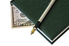 Dagbok med en reservoarpenna och del av en räkning 50 dollar Arkivfoton