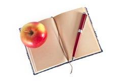 Dagbok med pennan och äpplet Arkivbilder