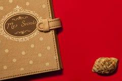 Dagbok mitt hemlighetfranska och snäckskal Röd bakgrund Arkivbild