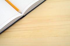Dagbok och blyertspenna på trätabellen Öppna en tom vit anteckningsbok på skrivbordet med utrymme för fri text Royaltyfri Bild
