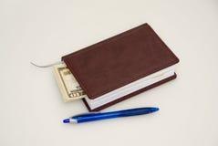Dagbok, penna och några dollar Royaltyfria Bilder