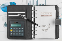 Dagbok, räknemaskin, gem och penna som ligger på en bakgrund av Fotografering för Bildbyråer
