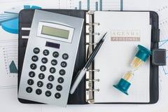 Dagbok, räknemaskin, timglas och penna Fotografering för Bildbyråer