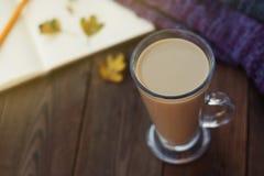 Dagboken, koppen av varm kakao, den varma halsduken och höstsidor på en träbakgrund kopierar sapce cozy isolerad white för höst b arkivfoto