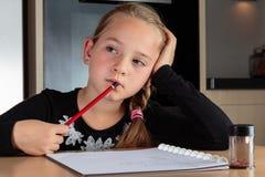 Dagdrömma flickan som gör läxa Arkivfoton