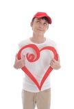 Dagdrömma hållande röd förälskelsehjärta för pojke arkivbilder