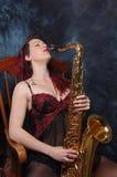 Dagdrömmaremodekvinna med saxofonen Fotografering för Bildbyråer