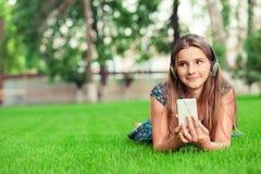 dagdromen Gelukkige jonge leuke studentenvrouw die met smartphonehoofdtelefoon op hoofd aan muziek luisteren die weg nadenkende p royalty-vrije stock fotografie