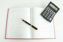 Dagelijks planboek dat uit met een vulpen en een calculator op het wordt uitgespreid stock fotografie