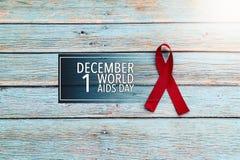 Dagen för världshälsa, bistår det röda bandet för medvetenhettecknet, kampen mot HJÄLPMEDEL undertecknar på den blåa träbakgrunde arkivfoton