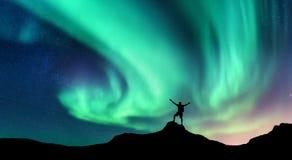 Dageraad en silhouet van de bevindende mens met opgeheven op wapens op de berg in Noorwegen Aurora Borealis royalty-vrije stock foto's