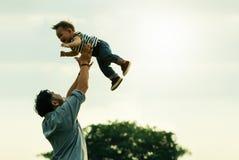 dagfader s Den lyckliga glade fadern som har gyckel, kastar upp i aien Royaltyfri Bild