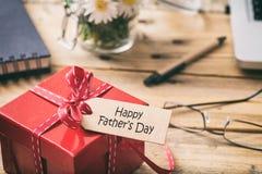 dagfader s Röd gåvaask med den lyckliga etiketten för fader`-dag, bakgrund för suddighetskontorsskrivbord Royaltyfria Bilder
