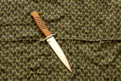 Dagger with wood handle against the background of green keffiyeh royalty free stock photo