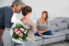 Daghter bringing flowers to her mother Stock Photography