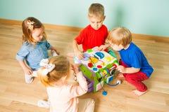 Dagisungar som spelar med att utbilda leksaken på ett trägolv royaltyfria foton