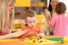 Dagisunge som lär med läraren i barnkammare arkivbilder