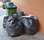 Daglig avfalls samlas och avskiljs in i påsehögar arkivbild