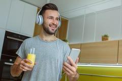 Daglig rutin för ungkarlman i det enkla livsstilbegreppet för kök som lyssnar till musik fotografering för bildbyråer