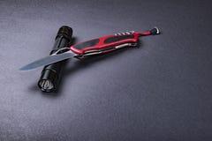 Dagligt bär EDC-objekt för män - öppnade vikningkniven, och den taktiska ficklampan på mörker försilvrar grå bakgrund royaltyfri fotografi