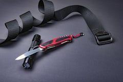Dagligt bär EDC-objekt för män - öppnade vikningkniven, taktisk ficklampa, och det svarta bältet på mörker försilvrar grå bakgrun royaltyfria foton