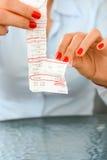 Dagligt kostnadsbegrepp med kvinnan som kastar ett pappers- skatte- kvitto Royaltyfri Foto