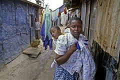 Dagligt livkvinnor med det rörelsehindrade barnet i slumkvarteret, Nairobi Royaltyfri Fotografi