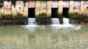 Dagligt livvideo efter regnet Vatten från en kanal i staden tappar ner till havet Att att tömma vatten och att förhindra floodin lager videofilmer