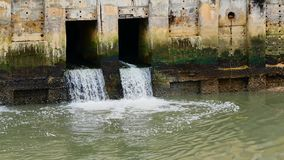 Dagligt livvideo efter regnet Vatten från en kanal i staden tappar ner till havet Att att tömma vatten och att förhindra floodin stock video