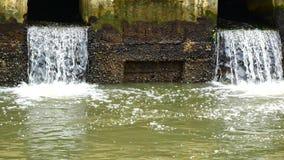 Dagligt livvideo efter regnet Vatten från en kanal i staden tappar ner till havet Att att tömma vatten och att förhindra floodin arkivfilmer