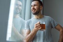 Dagligt rutinmässigt anseende för ungkarlman nära det enkla livsstilbegreppet för fönster som dricker att drömma för te royaltyfri bild