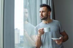 Dagligt rutinmässigt anseende för ungkarlman nära det enkla livsstilbegreppet för fönster som dricker att tänka för kaffe arkivfoton