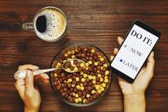 Dagplanläggning via smartphonen, medan ha frukosten arkivbilder