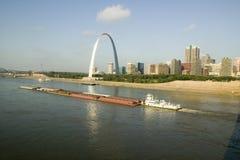 Dagsikt av den driftiga pråm ner Mississippi River för bogserbåtfartyg framme av nyckelbåge och horisont av St Louis, Missouri so Royaltyfria Bilder