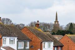 Dagsikt av helgedomkorskyrkan i den Daventry stadskärnan med typiska engelskahustak i förgrund Fotografering för Bildbyråer