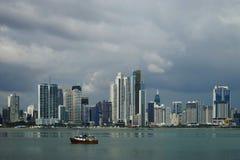Dagsikt av Panama City över den Panama fjärden med horisont och en fiskebåt på förgrunden Arkivbilder