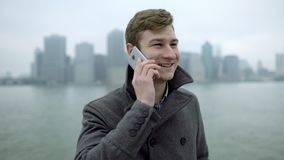 Dagsikt av turisten som talar över smartphonen med Manhattan på bakgrund arkivfilmer