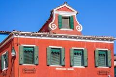 Dagsljussikt till den vibrerande röda fasaden av ett hus med prydnader Royaltyfri Foto