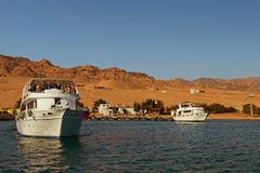 Cruise ship with tourists goes to the reef where people will dive with scuba diving or snorkeling. Dahab, Egypt – JANUARY 06, 2019: Cruise ship with royalty free stock photography