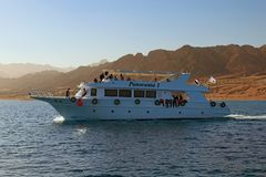 White cruise ship with tourists goes to the reef where people will dive with scuba diving or snorkeling. Dahab, Egypt – JANUARY 06, 2019: White cruise stock photo