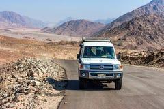 DAHAB, EGYPTE - AUGUSTUS 26, 2010: Toeristen in jeep in woestijn dichtbij Dahab, Egypte stock afbeeldingen