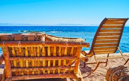 Dahab resort in Sinai, Egypt. The nice beach of Dahab with cozy rocking-chairs and bamboo benches of the local lounge zone, Sinai, Egypt stock photo