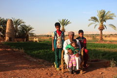Dakhla Oasis, Egypt - April 2nd of 2015: A bedouin family posing in front of the camera with their own land backwards. Royalty Free Stock Images