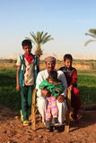 Dakhla Oasis, Egypt - April 2nd of 2015: A bedouin family posing in front of the camera with their own land backwards. Stock Photo