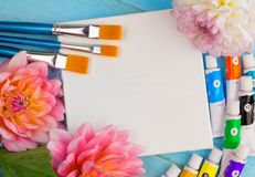 Summer background. dahlias, paints, brushes and a canvas on a blue wooden background. art. space for a text Stock Image