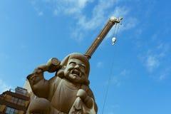 Daikoku向与起重机的雕象扔石头在背景中在神田寺庙在东京,日本 免版税库存照片